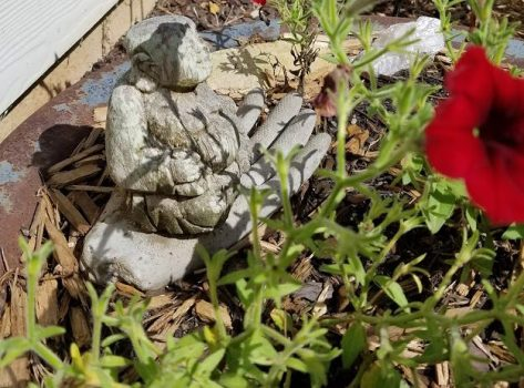 Small Buddha carving rests atop a concrete hand in a bowl filled with plants.